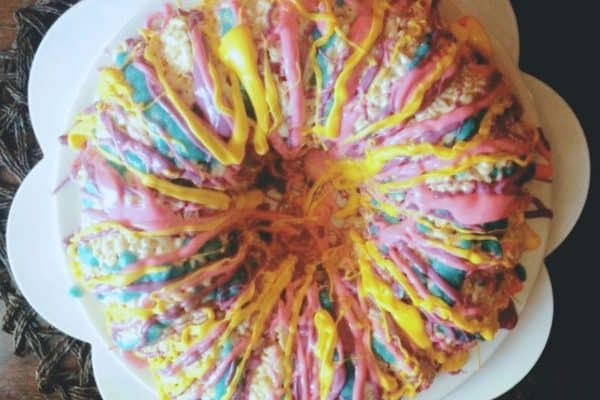 rice krispie cake with pink, blue, and yellow chocolates melted over it