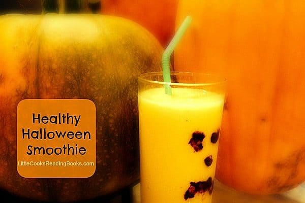 Halloween Drinks: Healthy Halloween Smoothie Recipe orange smoothie with a pumpkin face on the glass sitting in front of pumpkins