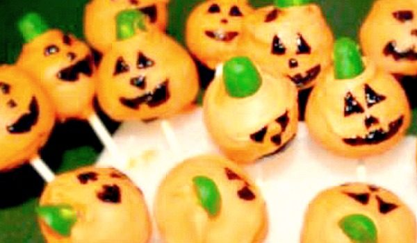 Pumpkin Cake Pops for Halloween pumpkin cake pops with faces sticking into a stand
