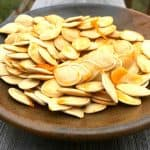 How To Prepare Pumpkin Seeds For Eating fresh pumpkin seeds in a bowl on a fence railing