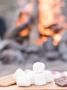 How To Make Smores graham crackers marshmallows chocolate smores ingredients with a fire behind it