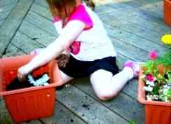 How to Make a DIY Container Fairy Garden for Kids of All Ages girl sitting on deck making a fairy garden in a container