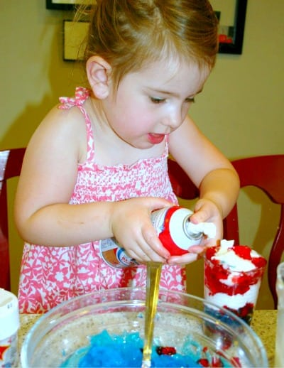 Red White Blue Layered Jello Cups are fun and easy with kids child using canned whipped cream on a red white blue dessert