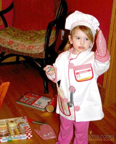 What age should a child learn to cook? toddler girl in a chefs outfit