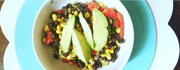 How To Make Black Bean and Corn Salad bowl with black bean and corn salad topped with avocado