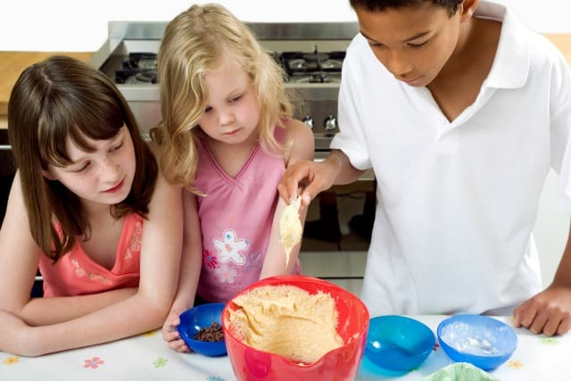 8 Surprising Places To Find Cooking Classes for Kids three kids making cookies