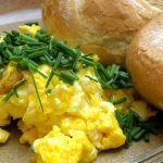 How To Make Scrambled Eggs on a plate with rolls