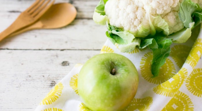 Use Granny Smith Apples for Apple Fries green Granny Smith apple on a white and yellow napkin on a table with vegetables
