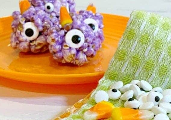 Easy Recipe for Popcorn Balls with Marshmallow For Halloween Treats purple people eater popcorn balls recipe on an orange plate
