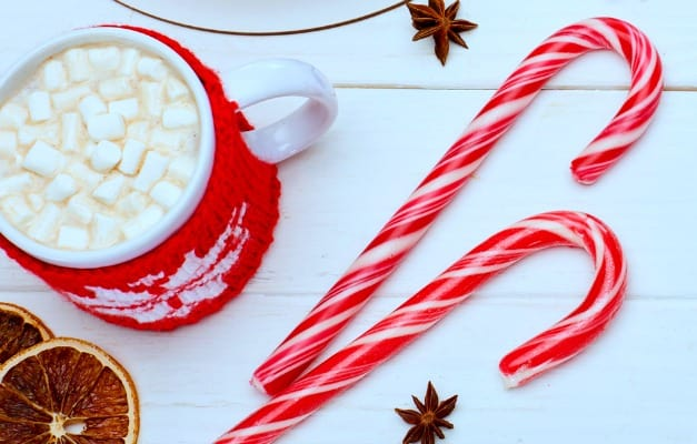 candy canes on a white table top sitting next to a mug of hot chocolate with marshmallows