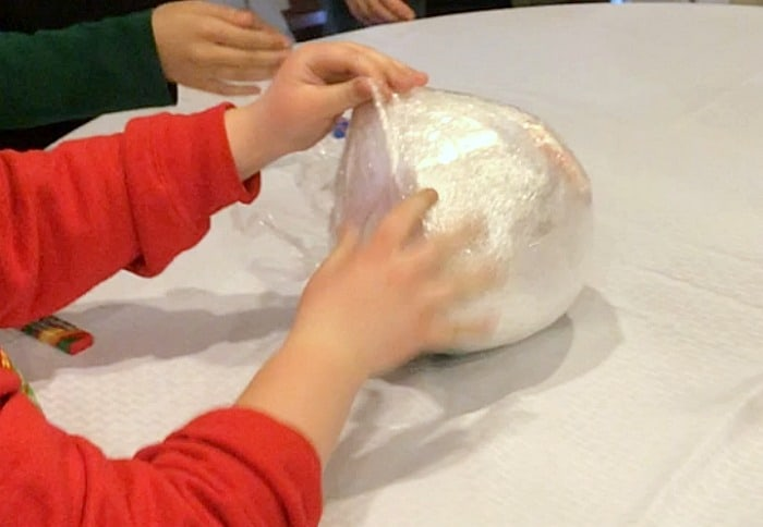 Saran Wrap Ball Game with hands unwrapping cellophane ball