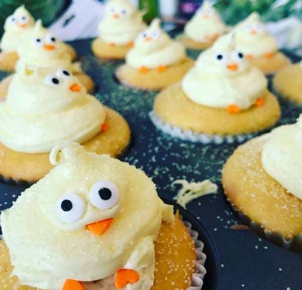 two rows of yellow cupcakes in a cupcake pan with baby chicks made of icing on top