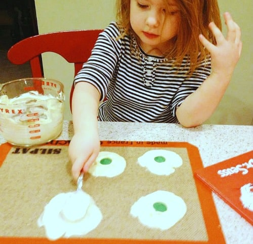 child spreading white chocolate onto a mat