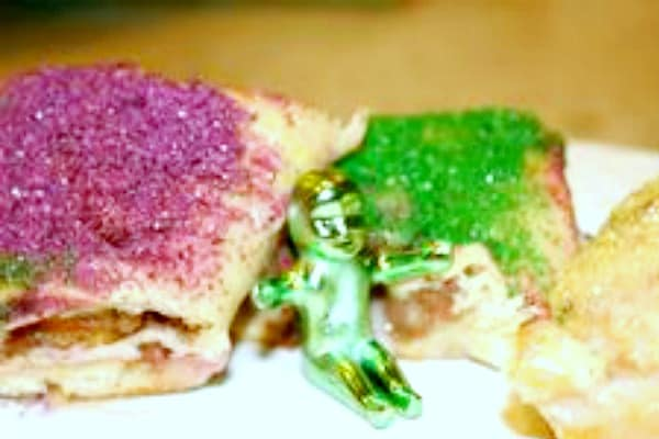 pieces of king cake with purple sugar icing and green purple icing with a tiny green plastic King Cake baby sitting between the two pieces of King Cake
