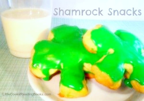 Shamrock St. Patrick's Day Desserts shamrocks made with croissant dough with green icing on a plate with a glass of milk