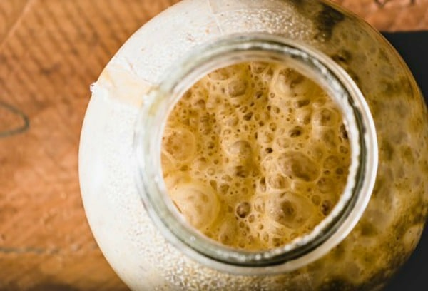How To Make Yeast At Home looking down at a glass with bubbling yeast liquid in it