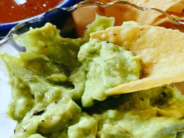 Homemade Guacamole a tortilla chip dipped into a bowl of guacamole