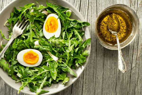 Dandelion salad with boiled egg in a bowl on a table with oil dressing in a cup next to it