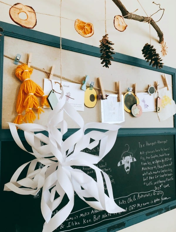 How To Make A Garland For Christmas dried fruit and pinecones hanging on twine over a bulletin board