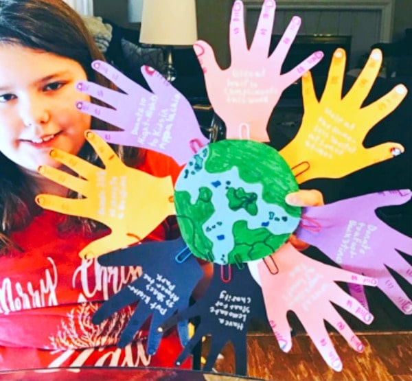 child with a helping hands craft of different colored cutout hand tracings attached to a world drawing