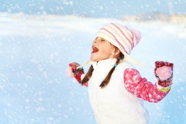 Snow Activities: young girl in winter hat and vest catching snowflakes on her tongue
