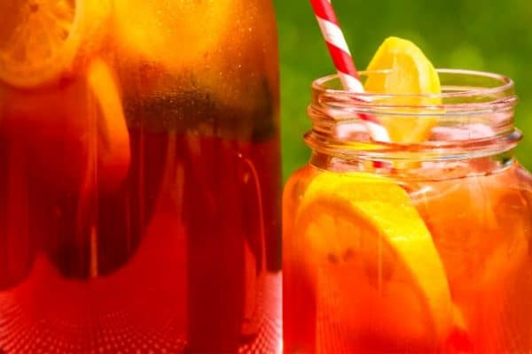 Sun Tea with full glass tea jar and sun tea in a mason jar with colorful straw sitting on picnic table on a summer day