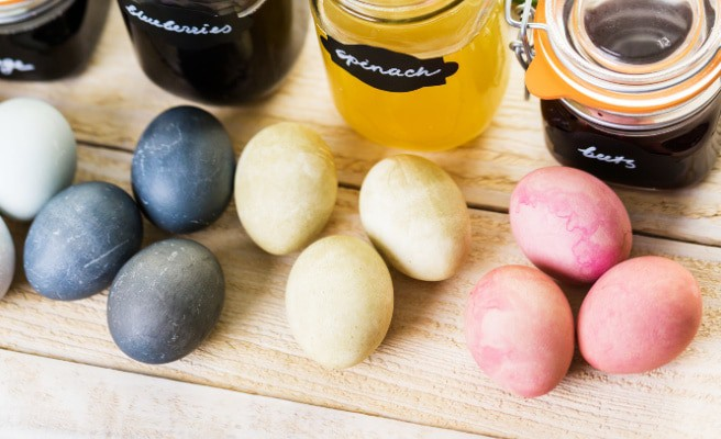 dye eggs naturally blue yellow and pink boiled eggs on a table dyed with food items