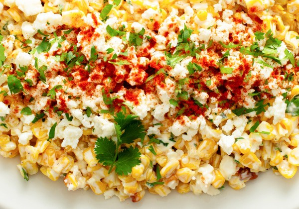 close up of Mexican Street Corn Off the Cob in a dish topped with cheese cilantro and chili powder