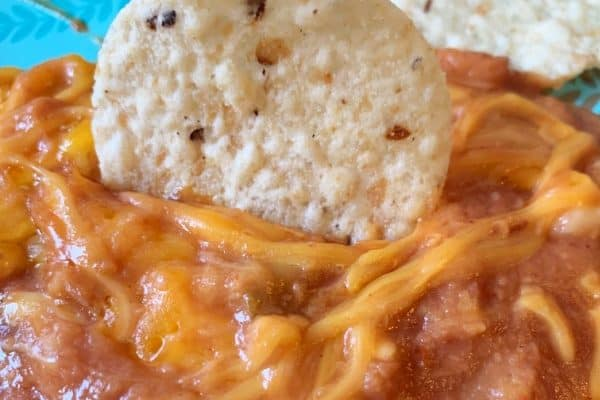 Refried Bean Dip with tortilla chip sticking in it