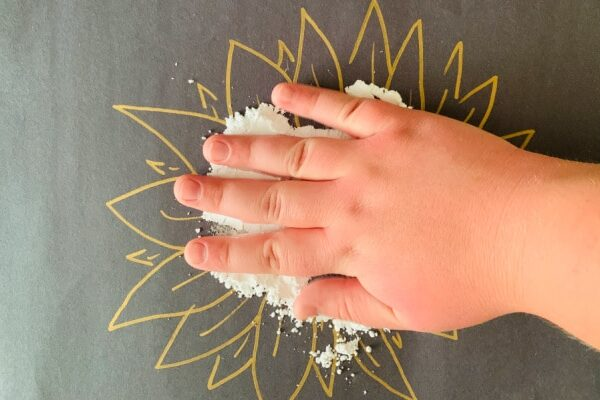 child's hand on black paper doing a Pollinator Craft