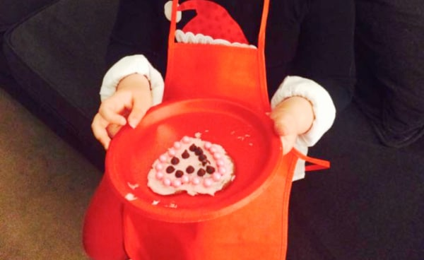 Sugar Cookie Recipe To Decorate for Cookie Party child's hand holding a decorated sugar cookie on a red plate
