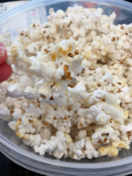 RECIPE FOR KETTLE CORN with fingers holding popped kettle korn
